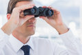 Serious businessman looking to the future with binoculars Stock Photo