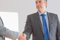 Serious businessman shaking a hand mature at office Stock Image