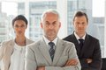 Serious businessman standing with colleagues behind arms folded Stock Photos