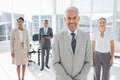 Serious businessman standing with colleagues behind him Royalty Free Stock Photography