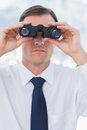 Serious businessman using binoculars in his office Royalty Free Stock Photo