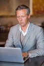 Serious businessman using his laptop at the cafe Stock Images