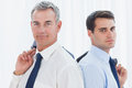 Serious businessmen posing back to back together while holding t in bright office their jacket Stock Photography