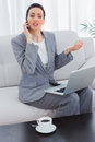 Serious businesswoman calling with her mobile phone and using laptop sitting on sofa at office Royalty Free Stock Photography