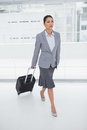 Serious businesswoman carrying her suitcase and walking Stock Photos