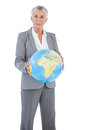 Serious businesswoman holding globe on white background Stock Photo