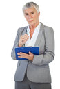 Serious businesswoman holding her clipboard on white background Stock Photo