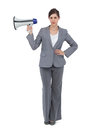 Serious businesswoman holding loudspeaker on white background Stock Image