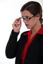 Serious businesswoman lifting glasses up her Stock Photography