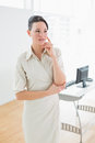 Serious businesswoman looking away in office as she stands the Royalty Free Stock Photography