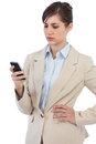Serious businesswoman posing with phone on right hand against white background Stock Images