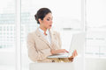 Serious businesswoman standing behind her chair holding laptop Royalty Free Stock Photo