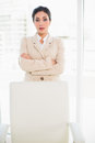 Serious businesswoman standing behind her chair in office Stock Photography