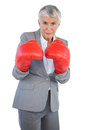 Serious businesswoman standing with her boxing gloves on white background Royalty Free Stock Photos