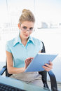 Serious businesswoman wearing glasses using tablet in bright office Royalty Free Stock Photography