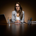 Serious businesswoman working late at desk Stock Images