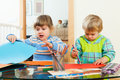 Serious children playing with paper and pencils
