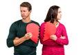 Serious couple holding cracked heart shape on white background Royalty Free Stock Photos