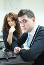 Serious couple working laptop looking at camera an Royalty Free Stock Photos