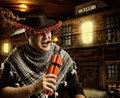Serious cowboy mexican firing dynamite by cigar for bank robbery at night Stock Photos