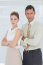 Serious coworkers posing together with arms crossed in bright office Royalty Free Stock Image