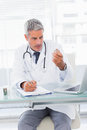 Serious doctor looking a medication for a prescription in medical office Royalty Free Stock Photography