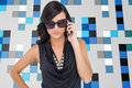 Serious elegant brunette wearing sunglasses on the phone composite image of Royalty Free Stock Image