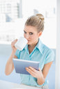 Serious elegant woman using tablet while drinking coffee in bright office Stock Images