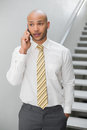 Serious elegant young businessman using cellphone against staircase in office Royalty Free Stock Photo