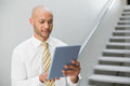 Serious elegant young businessman using digital tablet against staircase in office Royalty Free Stock Photo