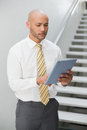 Serious elegant young businessman using digital tablet against staircase in office Stock Image