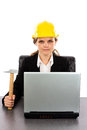 Serious engineer woman with a hammer sitting at desk against white background Royalty Free Stock Photography