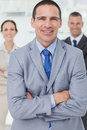 Serious entrepreneur posing with his colleagues on background in bright office Stock Photo