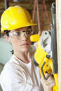 Serious female construction worker cutting wood with a power saw Royalty Free Stock Photo