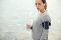 Serious female runner holding bottled water looking while a Royalty Free Stock Photos
