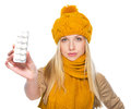 Serious girl in scarf and hat showing blister package of pills isolated on white Stock Photos