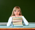 Serious girl with school books textbooks in against board Stock Images
