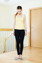 Serious girl standing on bathroom scales at home interior Stock Photos