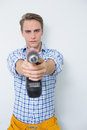 Serious handsome young handyman holding out drill portrait of a against white background Royalty Free Stock Image