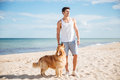Serious handsome young man with his dog on the beach Royalty Free Stock Photo