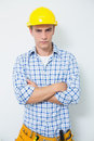 Serious handyman in yellow hard hat with arms crossed portrait of a against white background Stock Images
