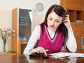Serious housewife filling in utility payments bills at home Stock Images
