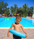 Serious kid stands near the pool in spa resort Stock Photography