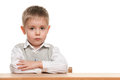 Serious little boy at the desk Royalty Free Stock Photos
