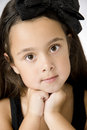 Serious little girl with big eyes resting chin on hands Stock Photo