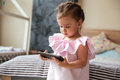 Serious little girl child indoors using mobile phone. Royalty Free Stock Photo