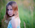 Serious little girl in field looking back over shoulder Stock Photography