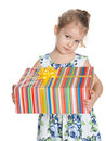 Serious little girl with a gift box holds on the white background Royalty Free Stock Image