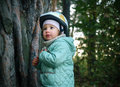 Serious little kid in a helmet looking up forest Royalty Free Stock Images