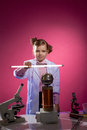 Serious little physicist shows focus with lamp on pink background Royalty Free Stock Image